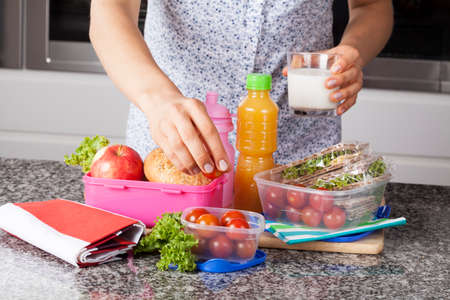 Young mother preparing healthy and tasty lunch box for child photo