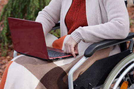 Elder woman on wheelchair using laptop in everyday life photo