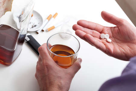 A closeup of taking pills washed down with whisky