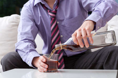 addiction drinking: An elegant man suffering from alcoholism drinking whisky Stock Photo