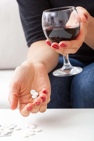 abusing: A closeup of a woman holding a glass of wine and a handful of pills