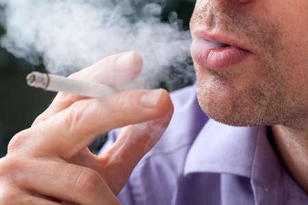 abusing: Un primer plano de un hombre exhalando humo de los cigarrillos � Foto de archivo