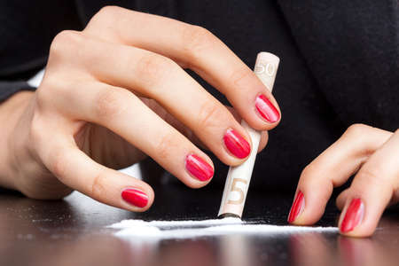 red gram: A hand of an addiced woman making a cocaine line using a note