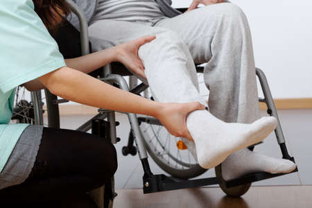 Jeune kinésithérapeute faisant de l'exercice avec une personne âgée handicapée