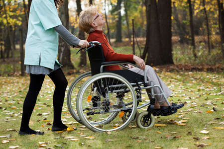 assisted living: Disabled senior woman with young nurse walking at park