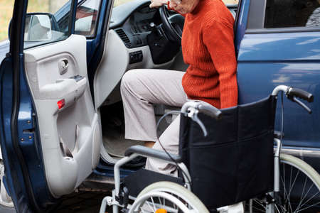 handicapped accessible: Disabled elder person driving car alone Stock Photo