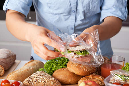 Young woman packing tasty sandwich with lettuce and ham photo