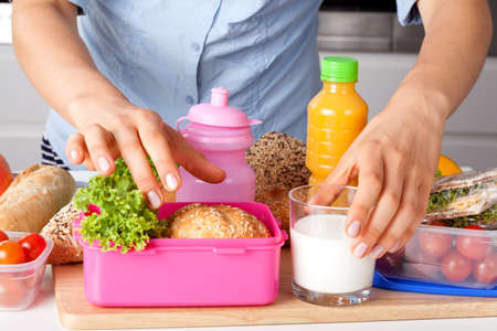 lunch time: Woman preparing healthy breakfast for school in the kitchen Stock Photo