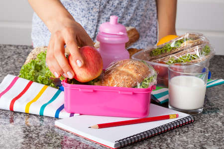 homemade bread: Woman preparing lunchboxes with fruits and sandwiches for school Stock Photo