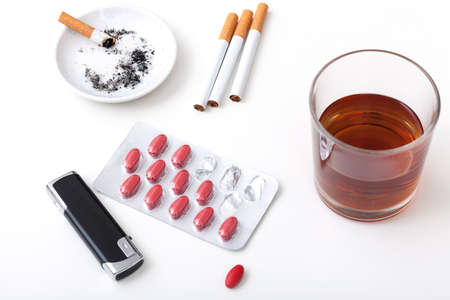 addictive drinking: A glass of whisky, cigarettes, pills and a lighter