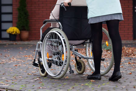 disabled person: Nurse walking with elder disabled person on wheelchair