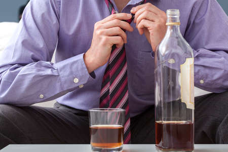 addictive drinking: A businessman about to have a drink after a tiring day at work Stock Photo