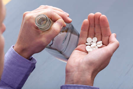 abusing: A pill-taker with a handful of tablets and vodka Stock Photo