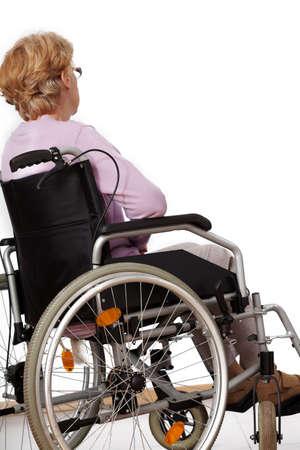 Elder disabled woman sitting alone on wheelchair photo
