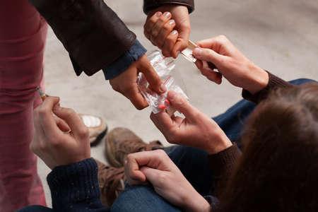 Молодой человек пристрастился к наркотикам, покупающих новые таблетки Фото со стока