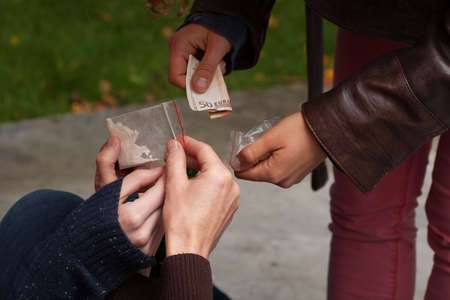 abuse young woman: Close up of young person selling drugs to youth