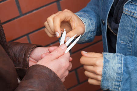 smoking: Student in brown jacket giving joint to colleague  Stock Photo