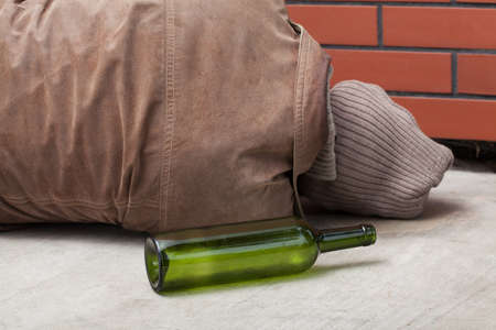 drunkard: A lying drunkard and and empty bottle Stock Photo