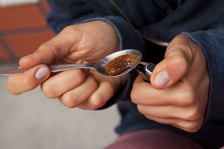 druggie: Primo piano delle mani della donna droga cucina con un accendino