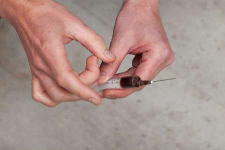éxtasis: Close up de las manos del hombre con la jeringa llena con la droga Foto de archivo