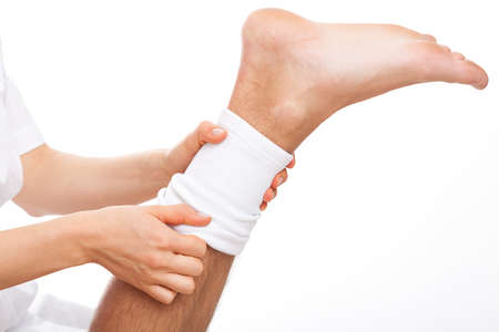 chiropodist: Physioterpist putting an elastic band on injured leg of patient