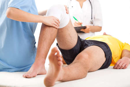 surgery doctor: Qualified medical team examining knee condition in clinic for athletes.