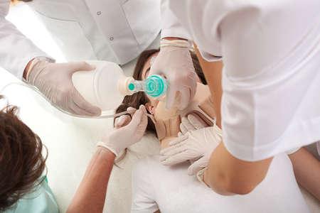 Team van artsen en paramedici proberen om een stervende vrouw terug tot leven te brengen. Stockfoto
