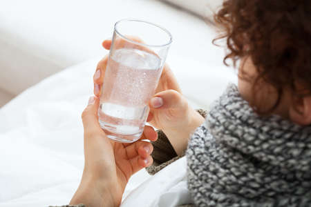 warm drink: Woman holding glass with water with soluble tablet