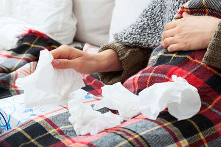 handkerchiefs: Person having a runny nose, sitting under blanket Stock Photo