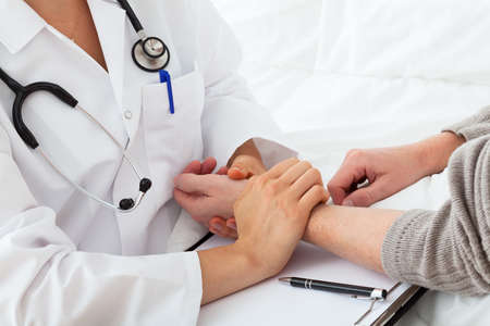 taking pulse: A doctor taking the patients pulse  Stock Photo