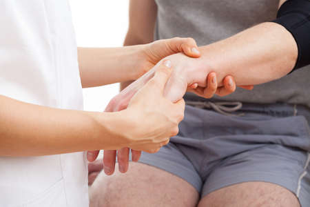 treating: Physiotherapist is treating a patient with hand ponds problems