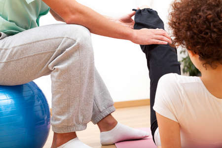 medical therapy: Doctor is stretching womans leg on physiotherapy session Stock Photo