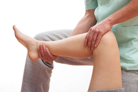 Physiotherapist massaging the legs muscles of young sportswoman photo
