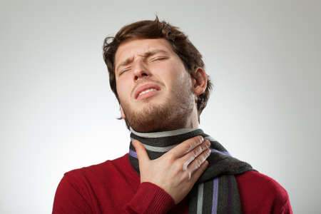 sore throat: Man in scarf suffering from sore throat