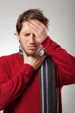 Man in red sweater and scarf has a strong flu symptoms  photo