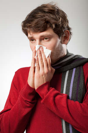 catarrh: Man isolated blowing nose because of illness Stock Photo