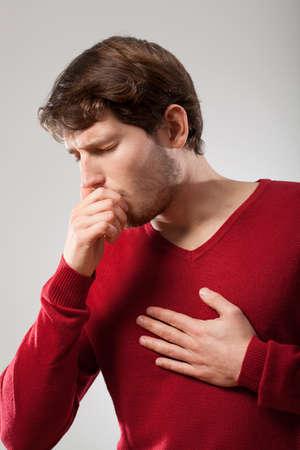 tosiendo: El hombre con pulmones enfermos celebración de su pecho y la tos Foto de archivo