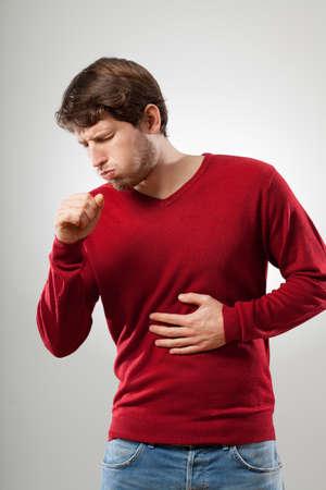 toser: Hombre con el desgaste de la gripe en la tos suéter rojo