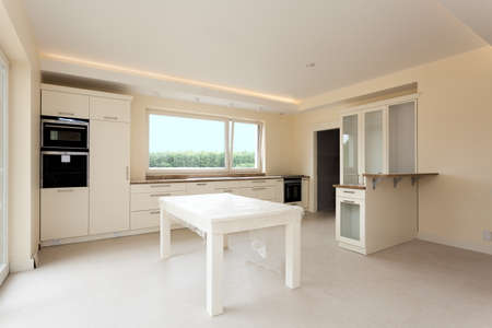 New kitchen interior with bright furniture and huge window photo