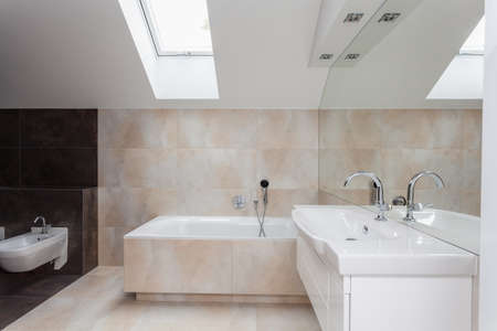 Bathroom interior with beige and brown tiles on walls photo
