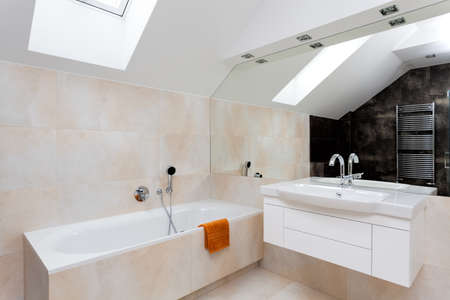 Bathroom with huge mirror, bath and white sink photo
