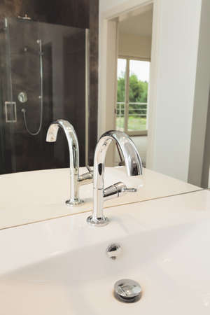Silver armature in bathroom - tap on a white sink Stock Photo - 24568143