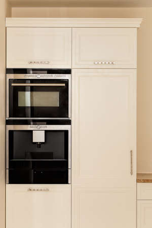 White furniture with black oven in modern kitchen photo
