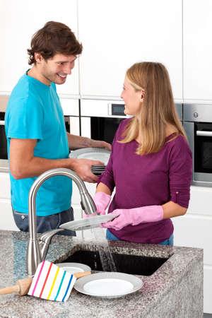 lavar trastes: Platos feliz y lavado de pareja juntos en la cocina Foto de archivo