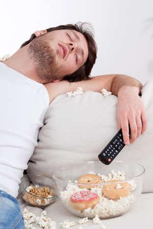 personen: Volledige jonge man slapen op een sofa met voedsel