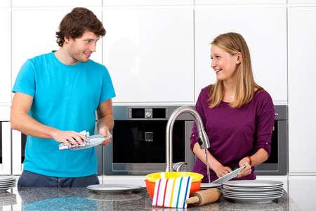 lavar trastes: Pareja joven limpieza juntos después de la cena Foto de archivo