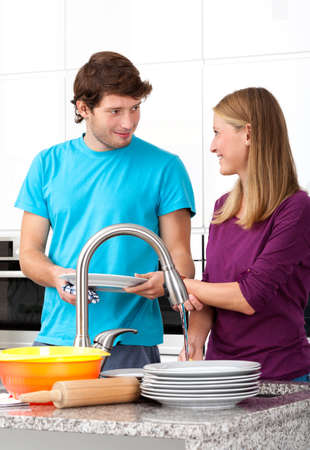 dish washing: Young man helping his wife in household duties