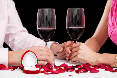 A closeup of glasses filled with red wine on a proposal evening photo