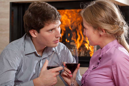 A couple proposing a toast with a red wine photo