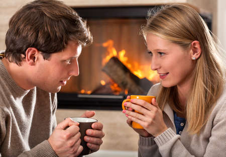 cosy: A couple warming up with hot drinks by a fireplace